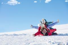 , Skidar snösolen och gyckel - den lyckliga familjen skidar på ferie royaltyfri bild