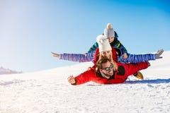 , Skidar snösolen och gyckel - den lyckliga familjen skidar på ferie royaltyfri fotografi