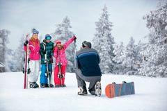 , Skidar snösolen och gyckel - familjen skidar på ferie som tar bilden fotografering för bildbyråer