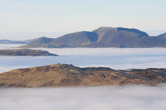 Skiddaw Fells from Helvellyn. High on the Lakeland tops looking across a temperature inversion that blankets the dales and valleys below. Skiddaw rises out of stock images
