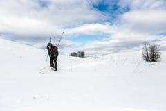 Skidåkarefotvandraren går ner kullen i häl för skogoskuld snowly Vinter som fotvandrar begrepp Många ställe för din text Arkivfoto