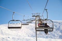 Skidlift cablechair med skidåkare på en solig dag skidar in semesterorten Royaltyfri Foto