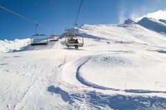 Skidlift cablechair med skidåkare på en solig dag skidar in semesterorten Royaltyfria Bilder