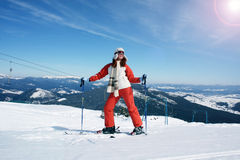 Skier. Young girl a skier stands on skis, smiles, looks at sky on a background mountains and ski lowering stock images