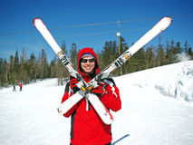 Skier. Standing with crossed skis with a blue sky background Royalty Free Stock Photo