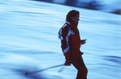 Skier in action 3. Female skier desceding a ski slope. Focus on the skier. Motion panned shot, on Velvia ISO 100, slightly grainy Stock Images