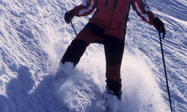 Skier in action. Descending a ski slope. Backlit Royalty Free Stock Photography