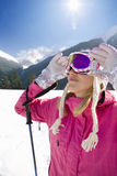 Skier adjusting goggles while standing in snow Royalty Free Stock Photos