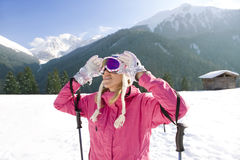 Skier adjusting goggles while standing in snow Stock Photo