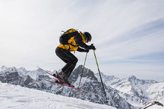 Skier admiring the mountains. Skier jumping on skis with a nice scenery on the background Royalty Free Stock Photos