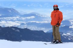 Skier in Alps. Adult male skier on snowy mountain with Alpine landscape in background Stock Photo