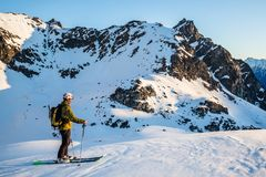 Skier in the backcountry of Alaska enjoying the first light of spring sunrise. A skier backcountry skiing in the Talkeetna Mountains of Alaska stops to enjoy the royalty free stock images