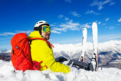 Skier with backpack sit on top of the mountain. Skier with backpack sit and rest on top of the mountain and look at the valley below Stock Images
