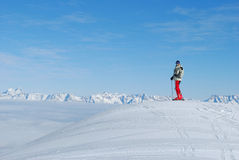 Skier at the beginning of a ski track. Male skier standing on top of a hill above clouds on a background of a mountain landscape Royalty Free Stock Images