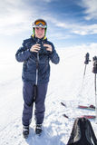 Skier with binoculars. Image showing a skier holding a pair of binoculars in his hand, during a break on a plateau Stock Photography