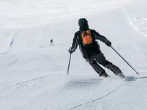 Skier in black downhill skiing on a ski slope. View from back.  Royalty Free Stock Image