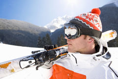 Skier carrying skis through snow royalty free stock photography