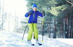 Skier child wearing a sportswear is skiing in winter forest stock image