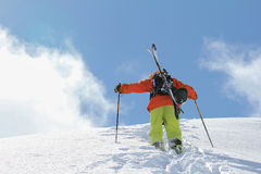 Skier climbing a snowy mountain Royalty Free Stock Photography