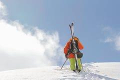 Skier climbing a snowy mountain Stock Photography