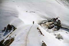 Skier climbing a snowy mountain Royalty Free Stock Photo