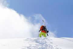 Skier climbing a snowy mountain Royalty Free Stock Image