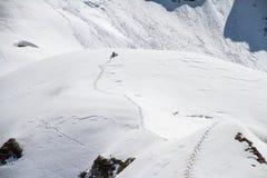 Skier climbing a snowy mountain Royalty Free Stock Photos