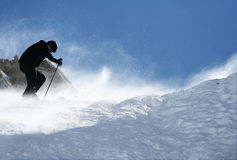Skier climbs on top of the mountain Stock Image
