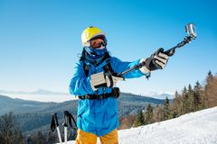 Male skier using selfie stick taking photos while skiing. Skier in colorful winter clothing taking a selfie with action camera on selfie stick posing on top of a Stock Photos