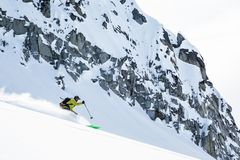 Skier cutting through fresh powder below granite cliff bands of the Talkeetna Mountains in the backcountry of Alaska. Skier in the backcountry of Alaska`s royalty free stock photo