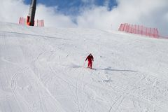 Skier descend on snowy sunlight ski slope at sun winter day. Greater Caucasus Mountains, Shahdagh, Azerbaijan royalty free stock images