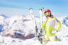 Skier in diving mask and snorkel standing on knees. Portrait of female skier in diving mask and snorkel standing on knees in snow bank against beautiful mountain Stock Image