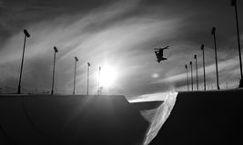 Skier doing an inverted trick in winter snow halfpipe Royalty Free Stock Photography