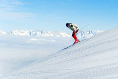 Skier downhill. Male skier moving down a ski track on a background of a mountain landscape Stock Image