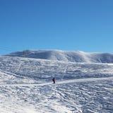 Skier downhill on snowy ski slope at nice sun morning. Georgia, region Gudauri. Caucasus Mountains in winter Royalty Free Stock Photos