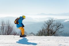 Skier skiing in the mountains. Skier enjoying skiing in mountains on a sunny winter day copyspace recreation active sport seasonal resort sportspeople adrenaline Stock Photography