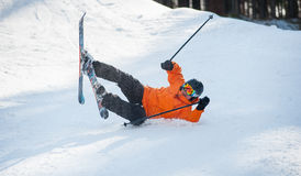 Skier fell in snow during the descent from mountain. Male is wearing orange jacket, helmet and goggles. Carpathian Mountains, Bukovel Stock Image