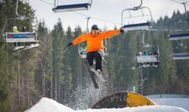 Skier flying over a hurdle in winter day. With forest of firs and ski lifts in background at a winter resort Royalty Free Stock Image