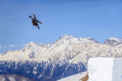 Skier flying from a ski jump making figure on blue sky and snowy mountain peaks background Stock Photos