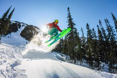 Skier freerider jumping from a snow ramp in the sun on a background of forest and mountains Stock Photos