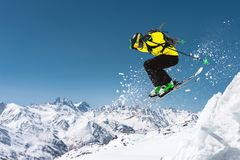 A skier in full sports equipment jumps into the precipice from the top of the glacier against the background of the blue. Sky and the Caucasian snow-capped Stock Photography
