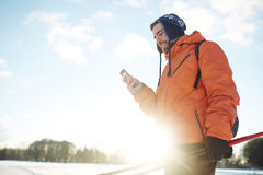 Skier with gadget Royalty Free Stock Photography