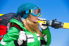 Skier girl portrait. Portrait of cute skier girl wearing sportive mask holding yellow ski over blue background, spending happy active winter holidays in the royalty free stock photo