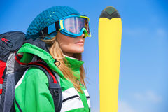 Skier girl portrait. Portrait of cute skier girl wearing sportive mask holding yellow ski over blue background, spending happy active winter holidays in the royalty free stock photography