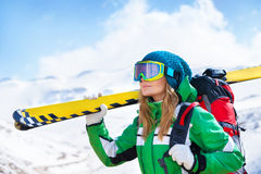 Skier girl portrait. Portrait of skier girl wearing special sportive outfit standing in snowy mountains, looking away, enjoying winter sport, healthy active stock photography