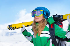 Skier girl portrait. Portrait of skier girl wearing special sportive outfit standing in snowy mountains, looking away, enjoying winter sport, healthy active royalty free stock photography