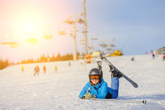 Skier girl on the snow at ski resort. Young happy skier girl in blue ski suit orange goggles and helmet lying on the snow at ski resort on a sunny day. Ski stock photos
