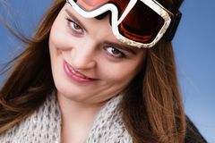 Skier girl wearing warm clothes ski googles portrait. Woman skier girl wearing ski googles portrait. Winter sport activity. Beautiful sportswoman on blue studio stock photo