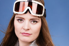 Skier girl wearing warm clothes ski googles portrait. Woman skier girl wearing ski googles portrait. Winter sport activity. Beautiful sportswoman on blue studio stock photos