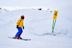 Skier goes to  warning signs of danger on  crossroads. Stock Images